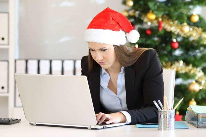 Angestelle mit Weihnachtsmütze auf dem Kopf blick mussmutig auf den Computer, weil ihr Arbeitgeber das Weihnachtsgeld streichen will