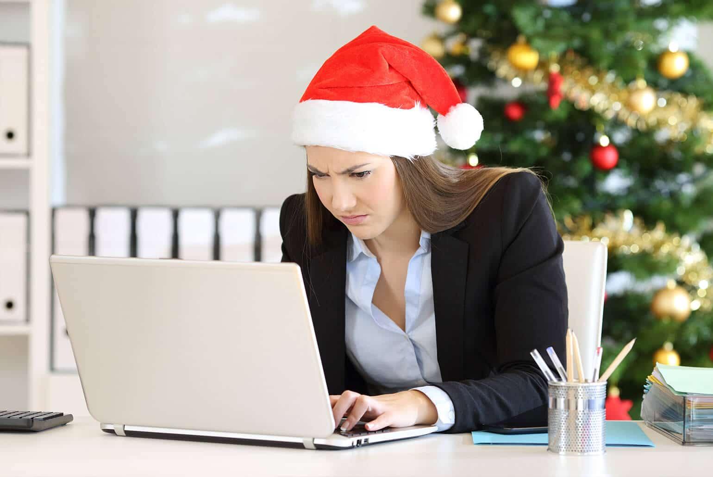 Angestelle mit Weihnachtsmütze auf dem Kopf blick mussmutig auf den Computer, weil sie kein Weihnachtsgeld erhalten hat