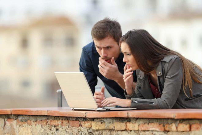 Zwei Personen sehen sich etwas im Laptop an nd solltend abei an die Gefahr einer Phishing Mail denken