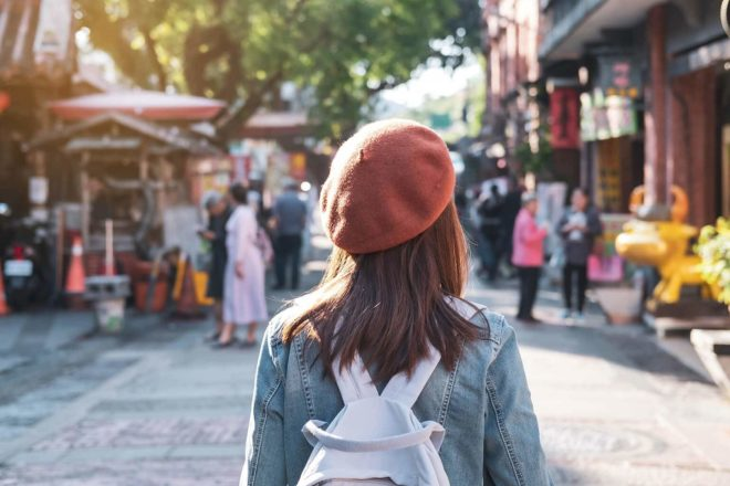 Von hinten abgebildete Frau mit roter Baskenmütze und weißem Rucksack läuft durch eine Fußgängerzone. Sie sieht wie jemand aus, der sich mit Kreativitätstechniken beschäftigt
