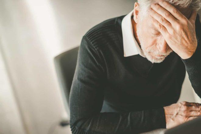 Erschöpfter Mann am Schreibtisch mit der Hand vor dem Gesicht. Er hätte besser in Burnout Prävention investieren sollen