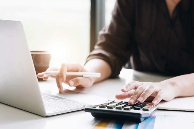 Unternehmer rechnet vor dem Laptop etwas mit dem Taschenrechner aus. Bei der Umsatzsteuer sollte er ans Vorsteuervergütungsverfahren denken