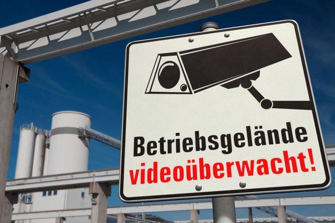 Schild mit Kamerasymbol warnt vor Videoüberwachung auf einem Firmengelände