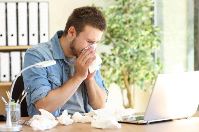 Mitarbeiter inmitten eines Haufens Taschentücher bei der Arbeit. festangestellte haben Anspruch auf Lohnfortzahlung bei Krankheit