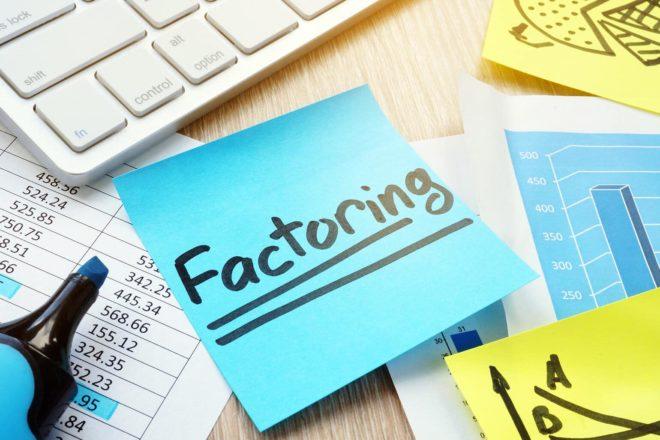 Zettel mit der Aufschrift Factoring liegt zur Erinnerung neben der Tastatur, ist aber keine Erklärung