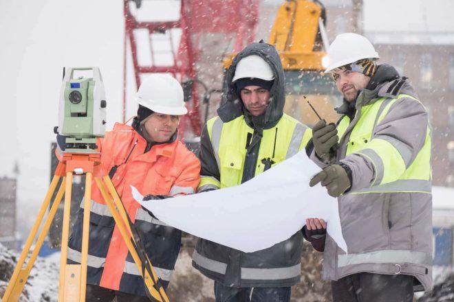 Drei Bautechniker mit Bauplan bei Schnee und Eis. Auf dem Bau müssen Unternehmer im Winter oft Kurzarbeit anmelden