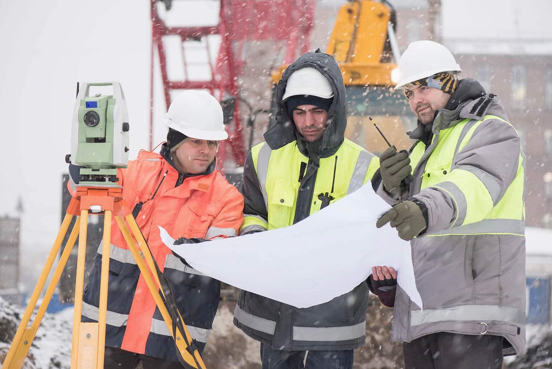 Drei Bautechniker mit Bauplan bei Schnee und Eis