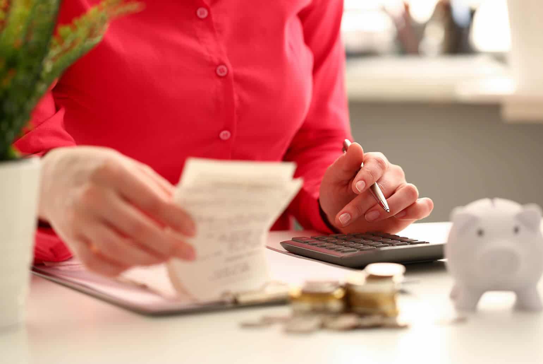 Die Chefin zählt Beträge zusammen und rechnet die Raten für den Kunden aus um mit ihm Ratenzahlung zu vereinbaren und den Vertrag abzuschließen