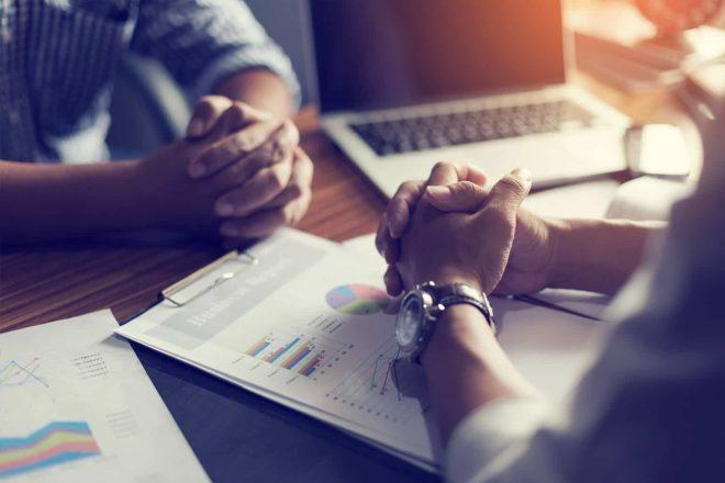 Foto mit zwei Personen im Gehaltsgespräch, die sich gegenübersitzen und der Fokus ist auf den Händen der beiden Gesprächspartner