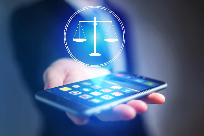 Hand mit Smartphone und Justiziasymbol darüber schwebend