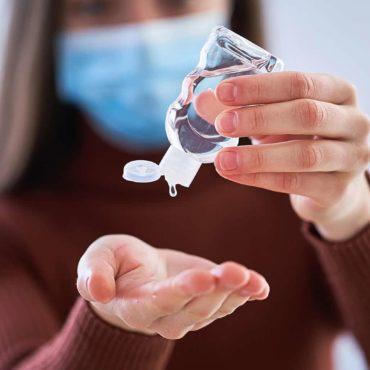 Foto einer Mitarbeiterin die sich die Hand desinfiziert