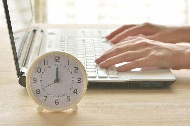 Das Bild zeigt Finger auf einer Computertastatur und davor einen Wecker als Symbol für elektronische Arbeitszeiterfassung
