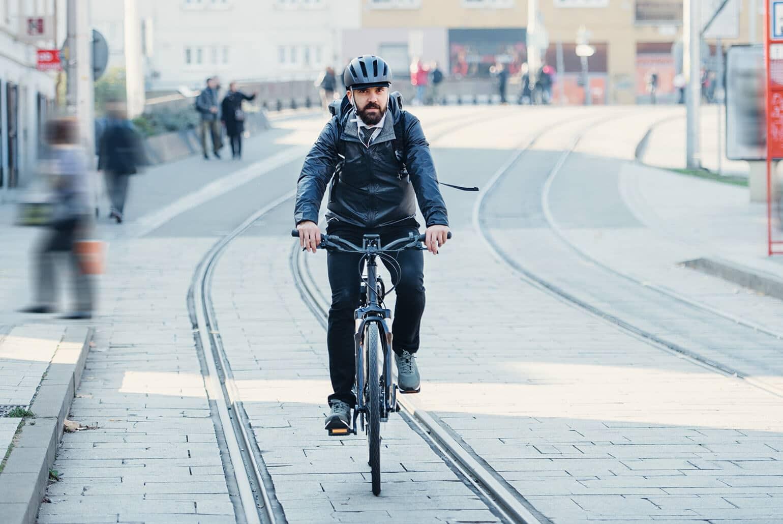 Das Foto zeigt einen Unternehmer, der mit dem E-Bike zur Arbeit fährt.