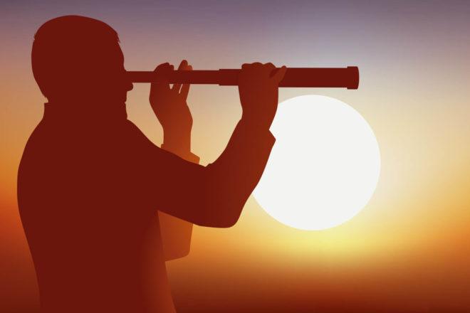 Mann schaut durch Fernrohr vor hell strahelnder Sonne. Gerade in Zeiten von Corona sollten Unternehmer ihre Strategie für die Zukunft hinterfragen