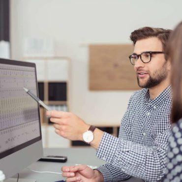Das Foto zeigt einen Mitarbeiter vor dem Computer, der einer Jobanwärterin etwas erklärt.