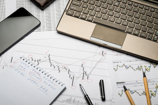 Foto zeigt Papiere mit Umsatzkurven, auf denen Stifte liegen und ein Laptop steht. Die Offenlegung und Veröffentlichung der Bilanz ist ein wichtiges Thema
