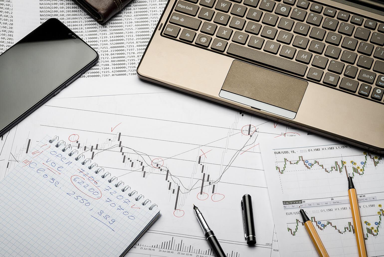 Foto zeigt Papiere mit Umsatzkurven, auf denen Stifte liegen und ein Laptop steht