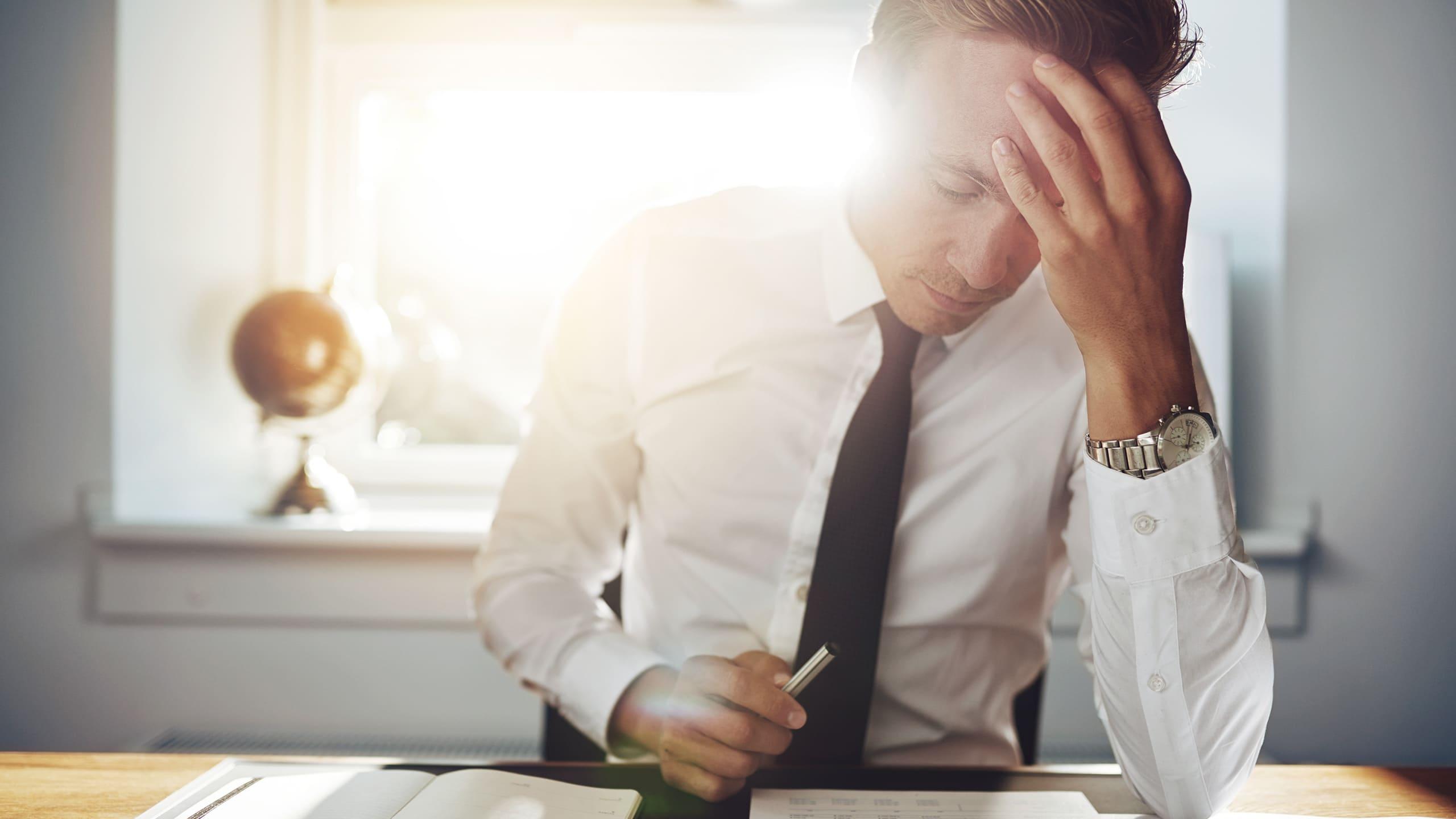 Bild zeigt einen Unternehmer dem am Schreibtisch sitzt und nachdenkt ob er die Corona Hilfe zurückzahlen sollte