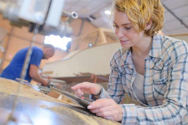 Foto einer Mitarbeiterin die in der Schreinerei mit einem Tablet die Arbeit vorbereitet, symbolisiert die Digitalisierung im Handwerk