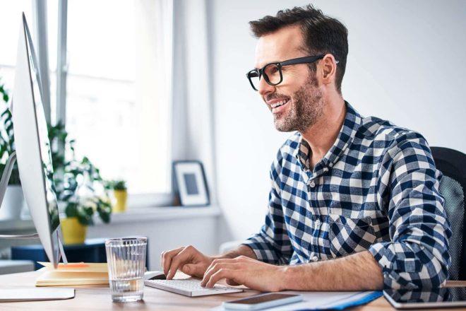 Das Foto zeigt einen Selbständigen, der am Computer arbeitet. Das Risiko einer Scheinselbständigkeit sollte ihm bewusst sein