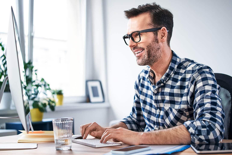 Das Foto zeigt einen Selbständigen, der am Computer arbeitet.