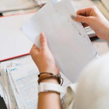 Zwei Hände über einem Stapel Rechnungen ziehen ein Blatt Papier aus einem Briefumschlag