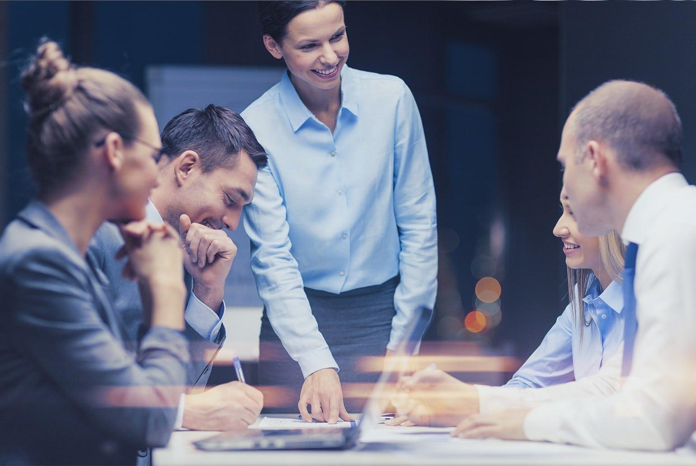 Foto zeigt Unternehmerin am Tisch die auf ein Papier zeigt und mit ihrem Team in freundlicher Atmosphäre etwas bespricht