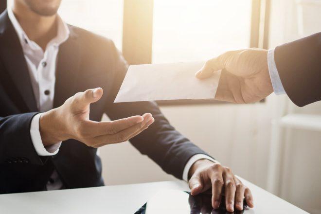 Das Bild zeigt den Geschäftsführer einer GmbH, der einen Umschlag mit seiner Abrechnung vom Gehalt in Empfang nimmt.