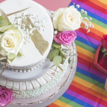 Foto zeigt Hochzeitstorte auf Regenbogenflagge denn das Allgemeine Gleichbehandlungsgesetz AGG sichert auch Homosexuellen Schadenersatz bei Diskriminierung zu, deshalb ist eine Schulung zum Thema nötig.