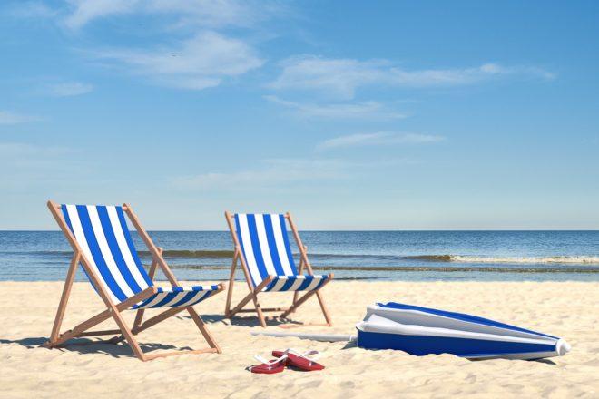 Foto mit zwei leeren Sonnenliegen am Strand zeigt das problem mit dem Urlaub nach Corona weil nicht klar ist ob Urlaiber kommen wollen oder nicht