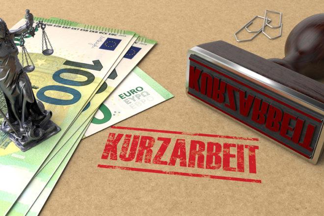 Foto zeigtgeldscheine und einen Stempel mit dem Wort Kurzarbeit als Symbol für die Auszahlung von Kurzarbeitergeld