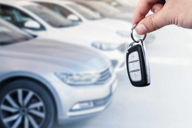 Das Foto zeigt eine Reihe von Firmenwagen. Eine Hand hält den Autoschlüssel. Betriebsprüfer gehen unterstellen eine verdeckte Gewinnausschüttung, wenn Unternehmer einen teuren Firmenwagen fahren, aber nur geringe Umsätze erwirtschaften.