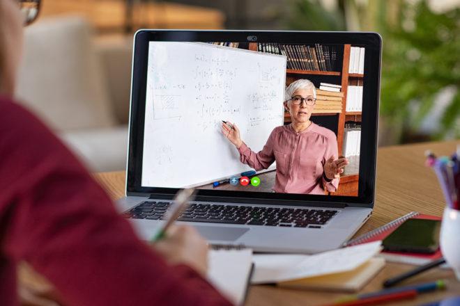 Foto zeigt vor einem Laptop sitzende Frau die digitale Beratung in Anspruch nimmt
