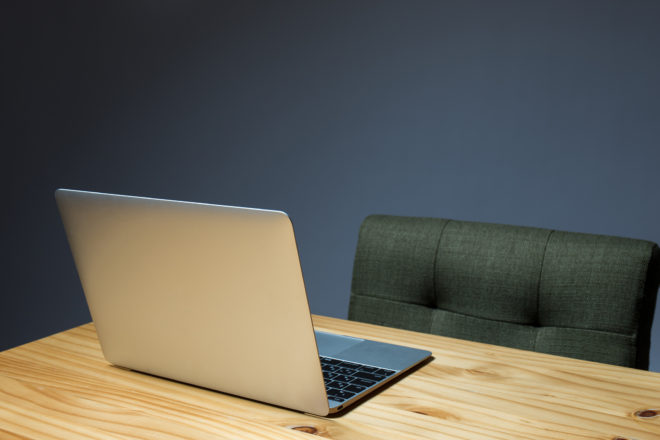 Das Foto von einem aufgeklappten Laptop in einem leeren Büro symbolisiert, dass niemand arbeitet und deshalb eine Abwesenheitsnotiz wegen Urlaub, Krankheit, Elternzeit oder Kündigung eingerichtet sein sollte