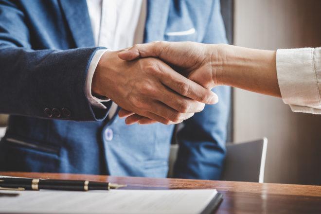 Das Foto zeigt, wie Unternehmer und Bankberater sich die Hände schütteln. Der Firmenchef bekommt frisches Geld, weil die Bank eine Bürgschaft beantragt. Diese dient als Sicherheit für die neue Kreditlinie.