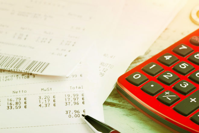 Foto zeigt einen Taschenrechner auf einem Stapel Kassenbons und soll symbolisieren, wie wichtig bei einer Kassennachschau eine Verfahrensdokumentation und eine Checkliste ist