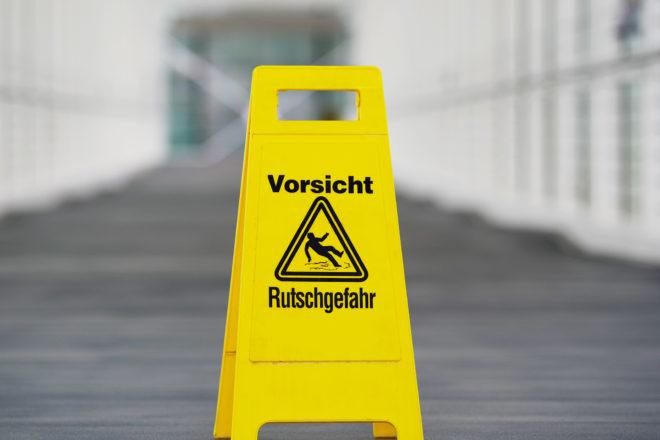 Mit einem Schild Rutschgefahr erfüllen Unternehmen die Verkehrssicherungspflicht in ihren frisch gewischten Räumen.