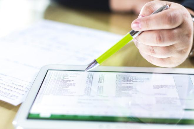 Foto zeigt die Hand eines Unternehmers über einem Tablet mit der elektronischen Rechnung oder E-Rechnung die nun Pflicht ist angezeigt