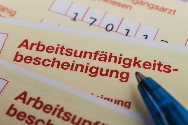 Foto von einem gelen Zettel zur Krankmeldung steht als Symbol dafür, dass eine krankheitsbedingte Kündigung nur unter bestimmten Voraussetzungen ausgesprochen werden darfDatev Trialog krankheitsbedingte Kündigung Voraussetzungen