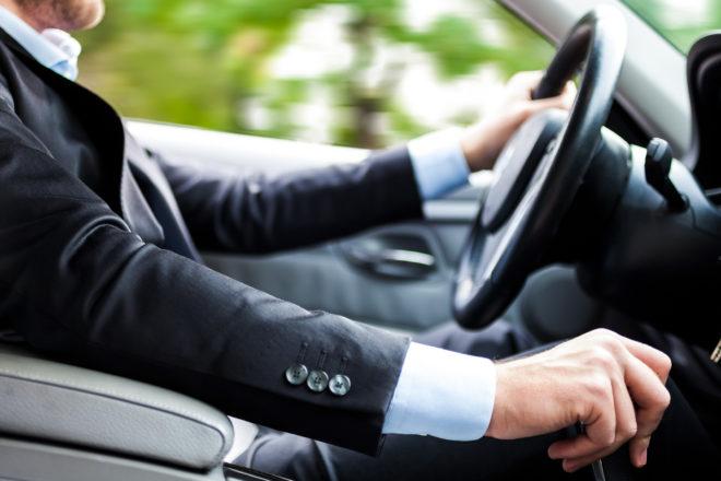 Das Bild zeigt einen Unternehmer, der mit dem Firmenwagen unterwegs ist. Die Privatnutzung muss er versteuern. Daher sollten Firmenchefs stets prüfen, was günstiger ist: Fahrtenbuch oder 1-Prozent-Regelung.