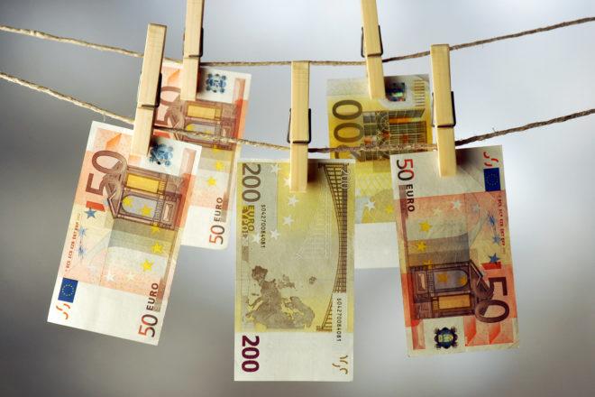 Foto zeigt mit Wäscheklammern befestigte Geldscheine rund um die Unternehmer mit Blick auf die Geldwäscherichtlinie neue Vorgaben beachten müssen