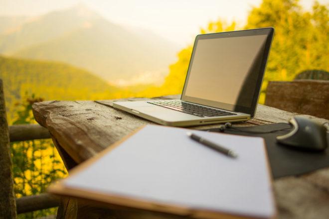 Bold zeigt einen offenen Laptop in freier Natur als Symbol für das Mobile Office