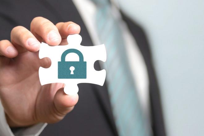 Hand hält ein Puzzleteil mit einem aufgedruckten Sicherheitsschloss als Symbol für die Abwehr von einem Angriff oder einer Attacke per Social Engineering