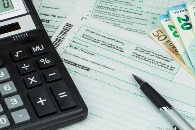 Foto zeigt das für die Berechnung eines Gesellschafterdarlehens nötige Handwerkszeug aus Taschenrechner und Stift über einem Steuerformular