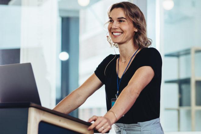 Foto zeigt eine strahlende Frau an einem Rednerpult als Symbol für ihr wie auch dem Betrieb nützenden Mitarbeitermotivation die Unternehmer auch im eigenen Interesse steigern sollten