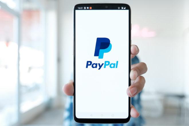 Foto zeigt eine Hand die ein Smartphone mit Paypal-Logo auf dem Bildschirm zeigt und über das Unternehmer und Verbraucher rasch per Paypal Kredit beanspruchen können.