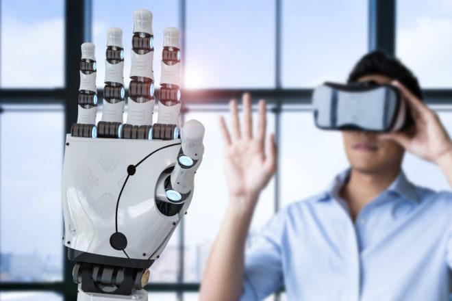Das Foto zeigt einen Mann der mit VR-Brille eine Roboterhand steuert als Symbol für Kompetenzmanagement das zu Höchstleistung befähigt