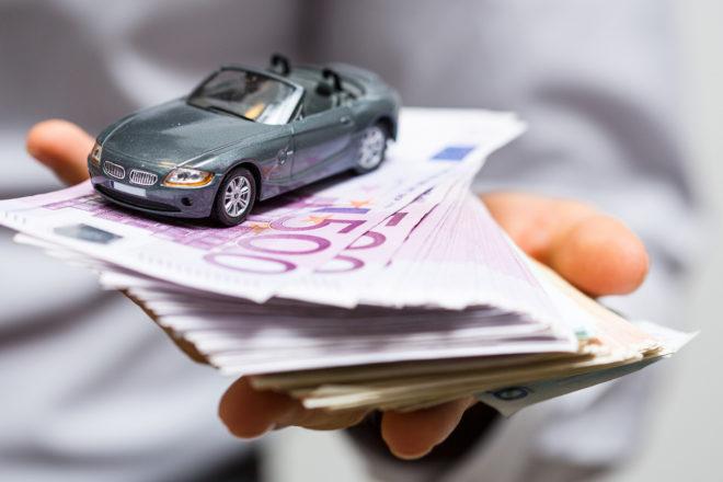 Foto zeigt eine Hand die ein Spielzeugauto auf 500 Euro Geldscheinen hält als Symbol für steuerfreie Zuwendungen durch den Arbeitgeber