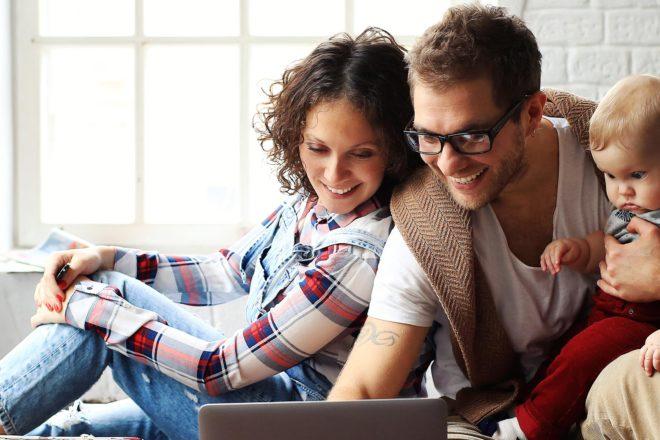 Foto zeigt junges Paar mit Baby am Laptop auf der Suche nach Informationen zum Thema Elterngeld für Selbständige