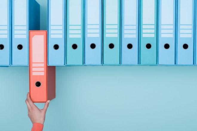 Grafik zeigt eine Hand die aus einer Reihe blauer Aktenordner einen roten Ordner für das Forderungsmanagement im Unternehmen zieht.